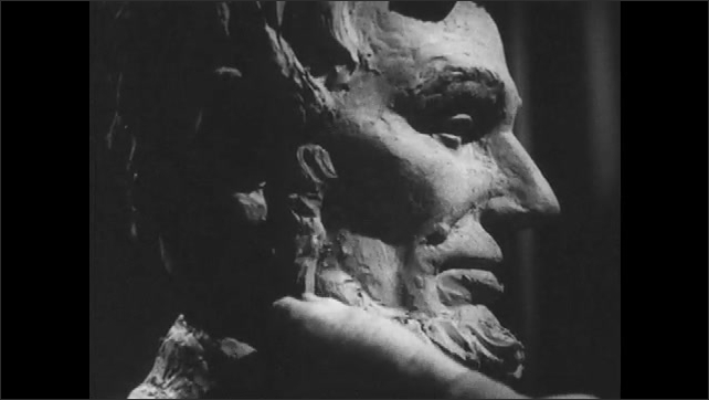 1950s: Hands sculpting clay bust. Close up, hands sculpting beard on face.
