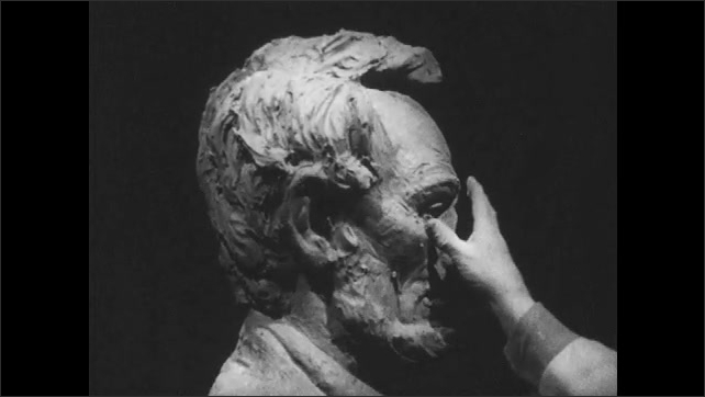 1950s: Close up, hands sculpting clay bust.