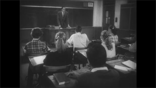 1950s: Students at desks, boy writing. Close up of boy. Teacher in front of class, teacher exits, boy stands.