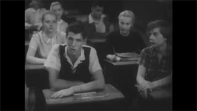 1950s: Close up of boy at desk. Teens at desks, girls talking.