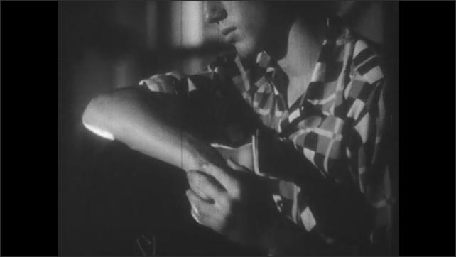 1950s: Close up of teen boy, tilt down to boy