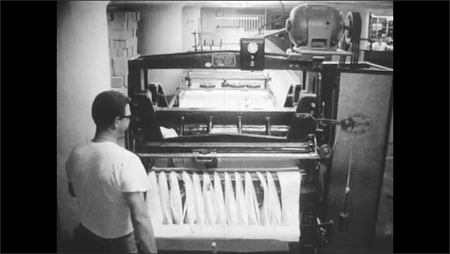 1960s: Man cuts fabric with power tool. Man watches machine cut strips of fabric.
