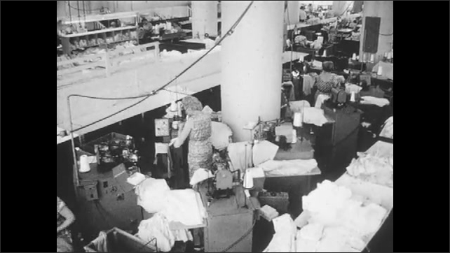 1960s: Women work in clothing factory, sew fabric.