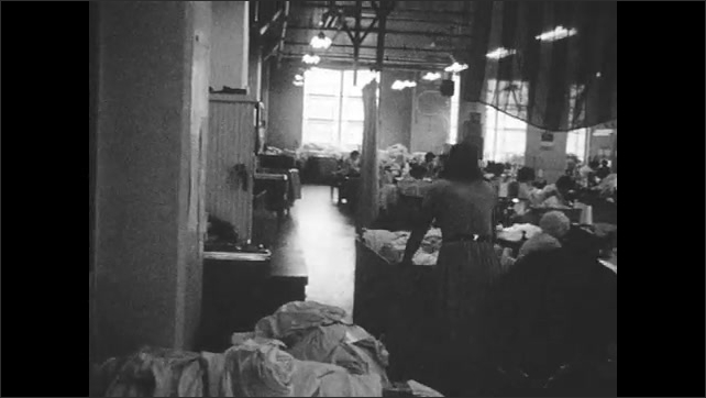 1960s: Woman pushes cart full of fabric through factory. Women sew at sewing machines.