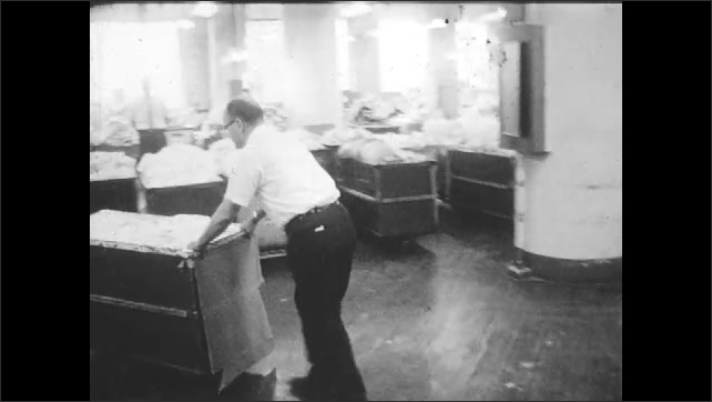 1960s: Woman retrieves shirts from machine, loads shirts into cart, man pushes through factory.