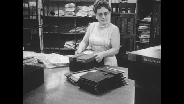 1960s: Women load stacks of packaged shirts into boxes.