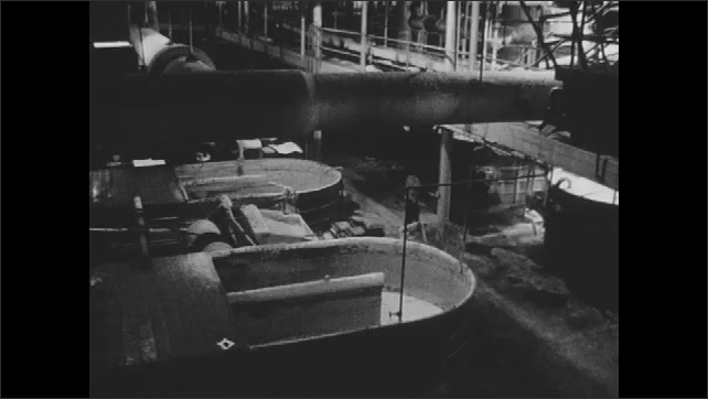 1960s: Factory.  Conveyor belt moves materials.  Man dumps paper into bin.  Man throws liquid onto machine.