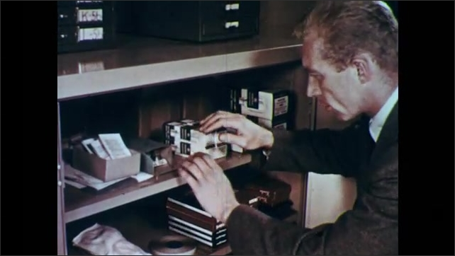1950s: UNITED STATES: operators move model of room and screen. Man looks through stock on shelf