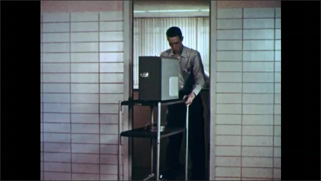 1950s: UNITED STATES: Introduction to Science title. Man speaks at reception desk. Man pushes projection trolley. Projectionist sets up film