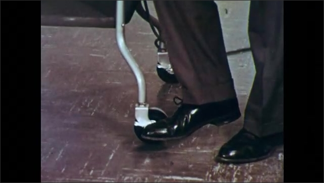 1950s: UNITED STATES: hand turns on projection motor and lamp. Man moves projector towards screen. Man places speaker on ground. Man attaches speaker cord