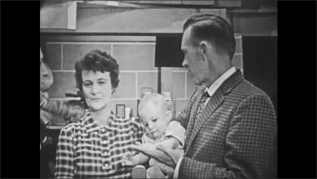 1960s: children in underground shelter playing with toys, man finishes interview with husband and wife