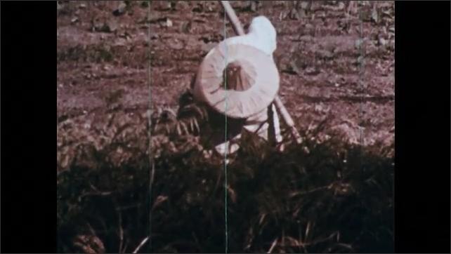 1960s: CHINA: farmer works soil in field. Man works in field.