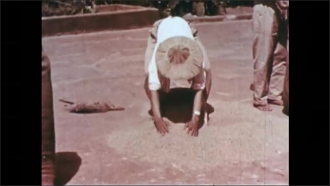 1960s: CHINA: man moves rice during drying process. Farmers put rice in sacks. Wagon loaded with rice.