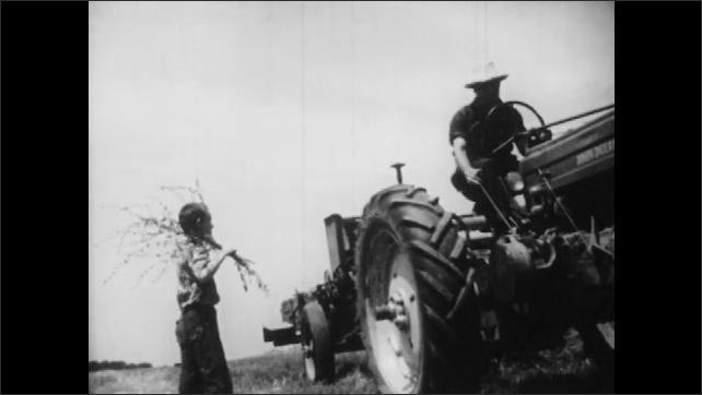 1950s: Man driving farm equipment, boy enters and talks to man, boy watches equipment drive away.