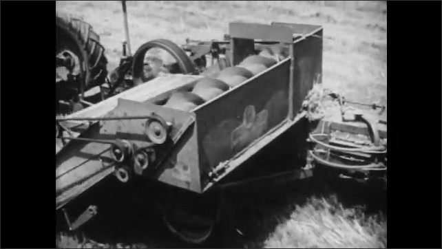 1950s: Close up, straw pulled into machine. Pan of farm equipment driving through field.