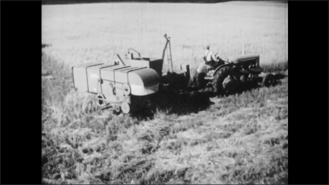 1950s: High angle view, farm equipment driving through field. Boy drives tractor pulling wagon.