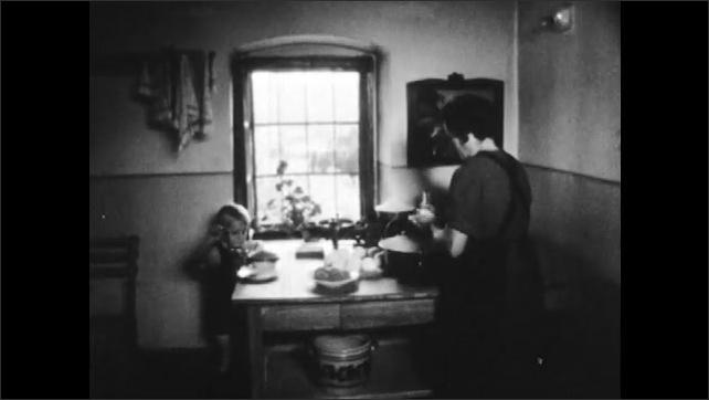 1950s: AUSTRIA: EUROPE: hands shape dumplings in bowl. Lady puts dumplings on table. Boy helps in kitchen. Lady puts dumplings in water