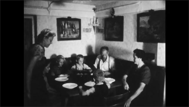 1950s: AUSTRIA: EUROPE: villagers carry scythes around house. Family sits down for meal. Boy eats food. Girl smiles.
