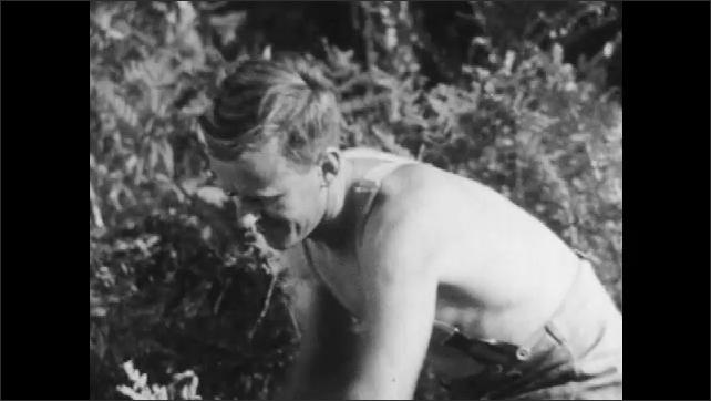 1950s: AUSTRIA: EUROPE: men cut branches from felled tree. Men cut bark from tree.