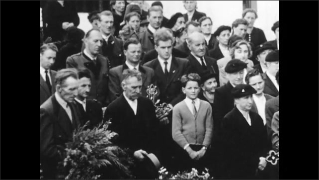 1950s: AUSTRIA: EUROPE: villagers attend funeral of neighbour. Man reads from Bible. Cross by grave. Man crosses self in church
