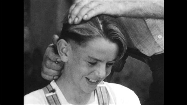 1950s: AUSTRIA: EUROPE: girl brushes hair. Boy gets hair cut. Man with moustache.