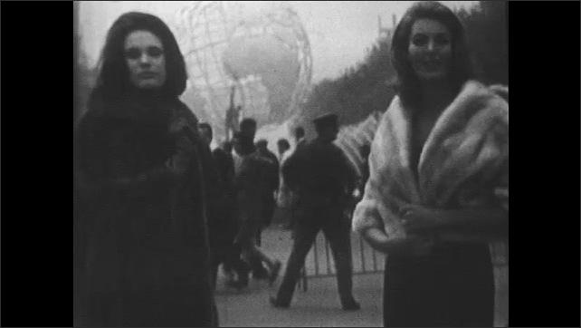 1960s: Women model fur coats in front of fountain.  Women turn and stroke coats.