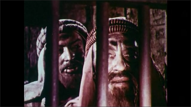 1950s: Two men with beards and head scarves stand behind bars talk. Man with beard and long hair standing behind bars talks. The two men walk away from the cell door.
