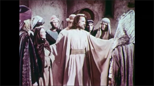 1950s: Man with beard and long hair speaking to crowded room of people wearing robes and head scarves.
