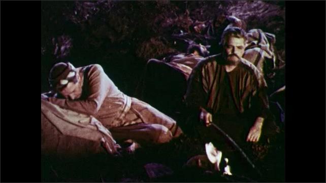 1950s: Man walking outside, pan to men sleeping, men sitting by fire.