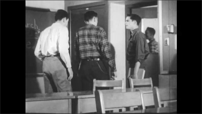 1950s: Classroom.  Teenage boys sit and talk.  Young man waits.  Boys walk past.  Door shuts in boy's face.
