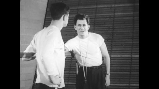 1950s: School gym.  Teacher and teenage boy speak.  Man gestures and taps young man on chest.  Man walks away.