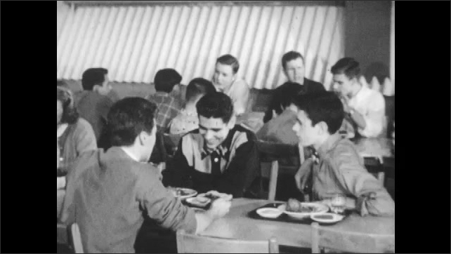 1950s: School cafeteria.  Boy carries tray.  Group of young men sit together and talk.  Students eat.  Young man sits alone.
