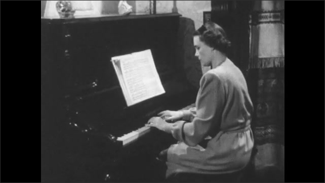 1950s: Woman sits at piano playing music as little girl stands behind her looking over her shoulder then walks away. Front door of house opens and hand drops letter on floor. Woman walk to door.