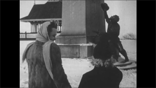 1950s: Young woman looks across river at factory. Woman and young woman hold hands and walk over to statue. Young woman climbs onto statue.