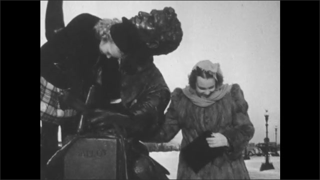 1950s: Girl sits on statue of man holding up hat, under the hat. Woman stands next to statue as girl plays and pulls out picture of man and looks at it.