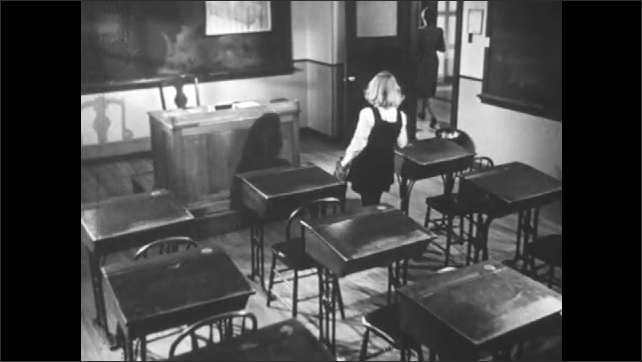 1950s: Girl and woman sit at desks in classroom. Teacher gets up and leaves and girl gets up to follow, but goes to teacher's desk instead.
