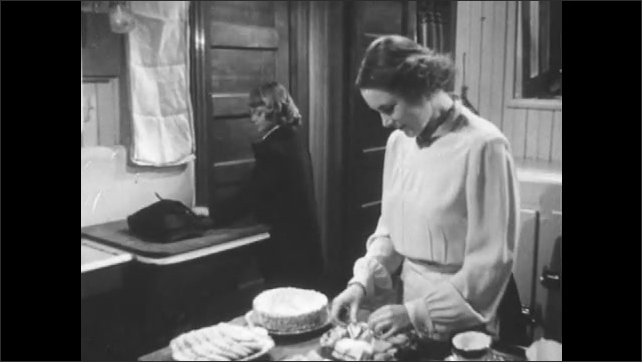 1950s: Girl enters front door of house and peers into room full of women then walks into kitchen. Woman in preparing desserts in kitchen when girl enters and hands her report card. Report card.