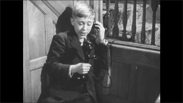 1950s: Boy walks over to phone and picks it up. He talks into phone then hangs it up.