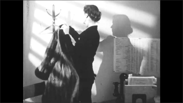 1950s: UNITED STATES: lady arrives at work. Lady hangs up coat in office. Lady sits at desk. Lady takes pencil from desk.