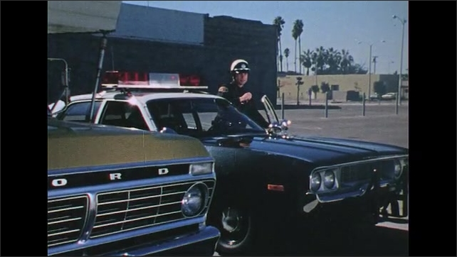 UNITED STATES 1970s: Man outside building, zoom out, men exit doors, walk with man / Police officer exits car, talks into radio, zoom in / Men walk to car.