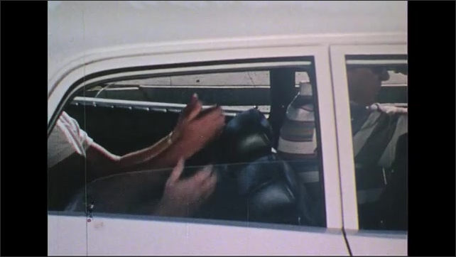 UNITED STATES 1970s: Police officer points gun behind car door / Man in car puts hands on dashboard / Men in back of car put up hands / Driver throws keys out window / Keys on street.