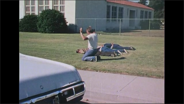 UNITED STATES 1970s: Police officer points gun behind car door, talks into radio / Men on ground, man lies down next to others / High angle shot, police officer runs to car.