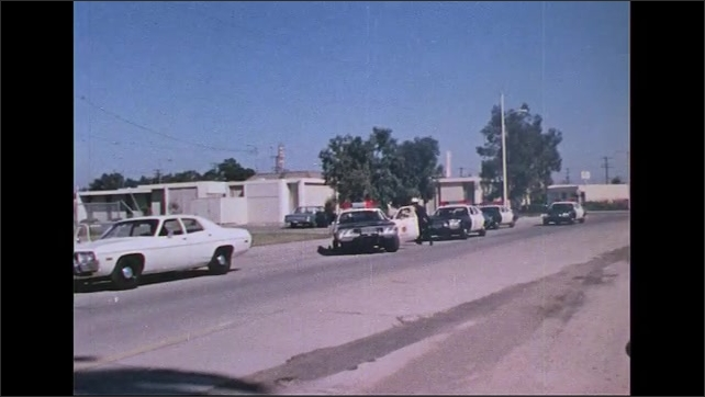 UNITED STATES 1970s: Police officer looks in car / Zoom out, officer backs up, police cars arrive / Officer with gun, zoom out to men on ground, police take positions.