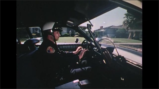 UNITED STATES 1970s: Car interior, police officer drives, picks up radio / High angle view, officer drives car.