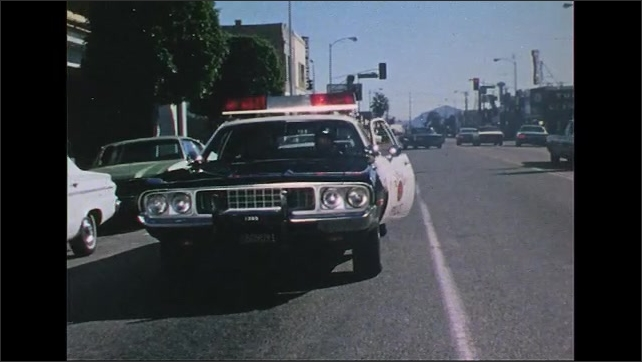 UNITED STATES 1970s: Man outside building / Police car pulls up, officer exits / Close up of officer / Men exit doors.