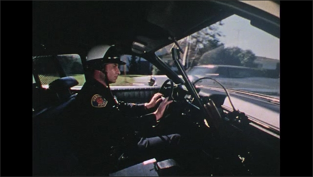 UNITED STATES 1970s: Car interior, police officer driving.