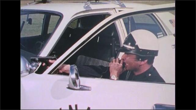 UNITED STATES 1970s: Police officer points gun behind car door, talks into radio.