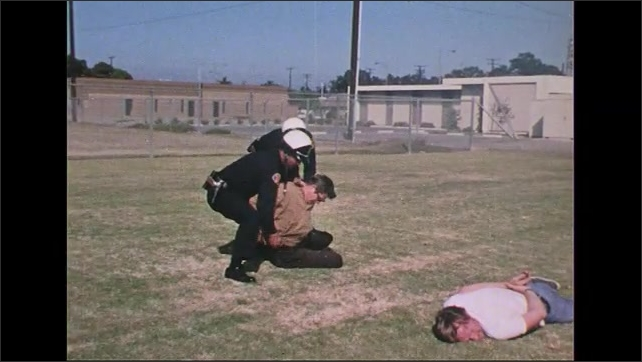 UNITED STATES 1970s: Police officer handcuffs man on ground, takes gun, other officer leads man away.