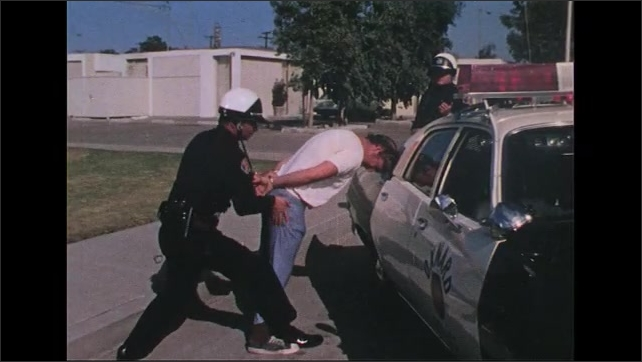 UNITED STATES 1970s: Police officer pats down man, puts him in car / Officer driving car.
