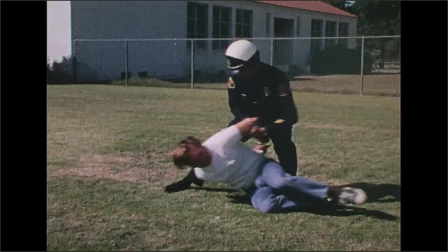 UNITED STATES 1970s: Police officer handcuffs man on ground, lifts him up, takes gun.
